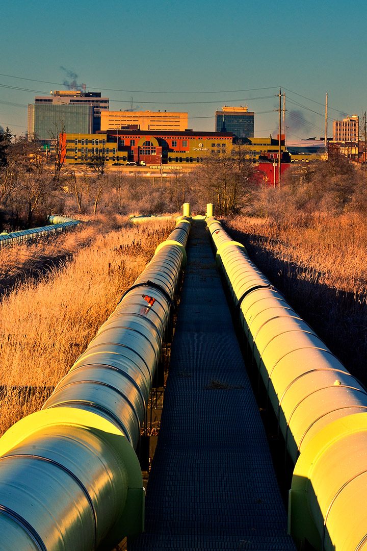 Two large water pipes running across a field in parallel.